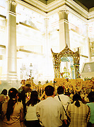 Worshipping at the Erawan Shrine with luxury mall behind