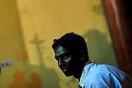 An alter boy sits under the shadow of a cross as he takes part in a late night Easter mass at the Our Sister of Charity church in the town of Raikia in the state of Orissa, India, April 12, 2009. Tensions remain high in the area several months after violence by Hindu fundamentalist towards the Christian minority forced thousands from their homes and leaving several churches and thousands homes across the state destroyed.
