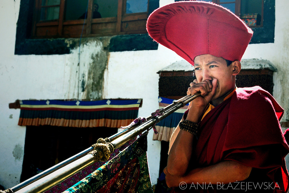 India, Ladakh. Young monk from Phyang monastery playing trumpet during the ceremony.