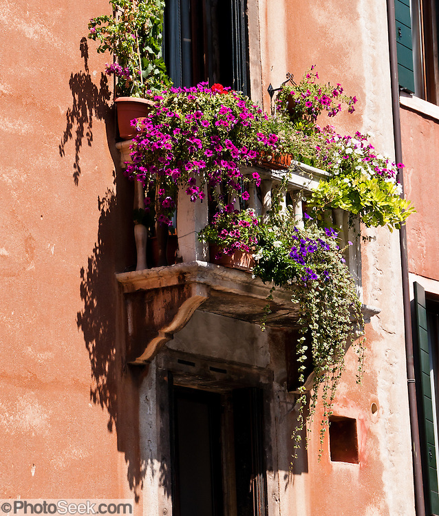 """Flower boxes bask in sun on a window balcony. Venice (Venezia) is the capital of Italy's Veneto region, named for the ancient Veneti people from the 10th century BC. The romantic """"City of Canals"""" stretches across 117 small islands in the marshy Venetian Lagoon along the Adriatic Sea in northeast Italy, Europe. The Republic of Venice wielded major sea power during the Middle Ages, Crusades, and Renaissance. Riches from Venice's silk, grain, and spice trade in the 1200s to 1600s built elaborate architecture combining Gothic, Byzantine, and Arab styles. Venice and the Venetian Lagoons are honored on UNESCO's World Heritage List."""
