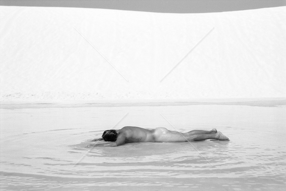 nude man cooling off in a pool of water in the desert