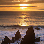The sun begins to set over the Pacific Ocean and sea stacks at the Marin Headlands, located at Rodeo Beach in the Golden Gate National Recreation Area near San Francisco, California.