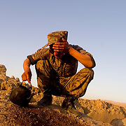 An Afghan solider wipes his face after a day of front-line fighting.