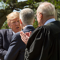 U.S. President Donald J. Trump shakes hands with Associate Supreme Court Justice Neil Gorsuch, as Supreme Court Justice Anthony Kennedy, who swore him in, looks on in the Rose Garden of the White House. Gorsuch replaces the seat vacated by Antonin Scalia when he died.