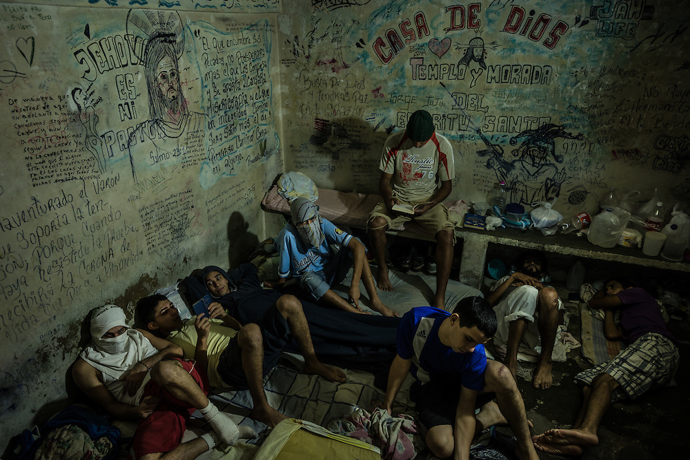 SAN ANTONIO DE LOS ALTOS, VENEZUELA - NOVEMBER 14, 2016: Men pass the time resting and reading in a jail in the outskirts of Caracas.  The majority in this cell were arrested for stealing, and had held regular jobs their entire lives, but turned to crime once the economic crisis sharply devalued their salaries, and they could not afford to support their families anymore.  Conditions in Venezuelan jails are inhumane. Those detained have to rely on family members to bring them food and water and personal items, but most come from working class families that are struggling to eat because of the economic crisis and skyrocketing food prices in Venezulea - that most cannot spare food to bring to their family members, or pay the bus fare to bring it to them.  The men said they are always hungry. They showed signs of being undernourished, and claimed to have lost dozens of pounds each since being detained.  The jails are overcrowded and the justice system is over capacity for processing cases, causing men in local jails to wait several months, and some several years, before having their case processed.  PHOTO: Meridith Kohut for The New York Times