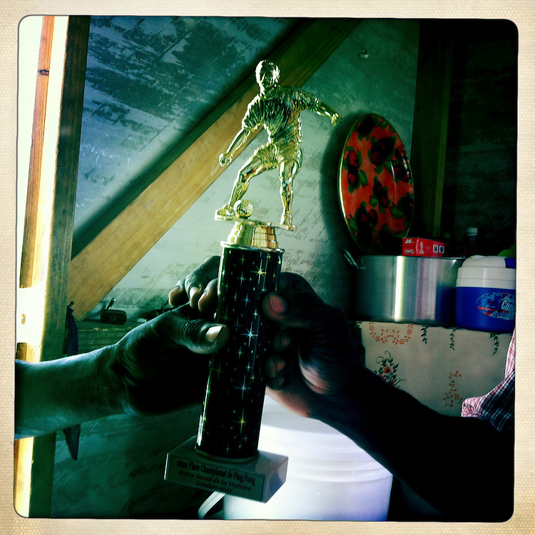 Men hold a soccer trophy at the Corail camp on Monday, April 2, 2012 in Port-au-Prince, Haiti.