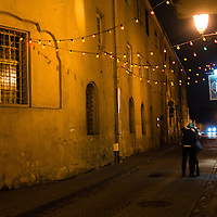 A couple embraces on the streets outside a pub in downtown Vilnius, Lithuania