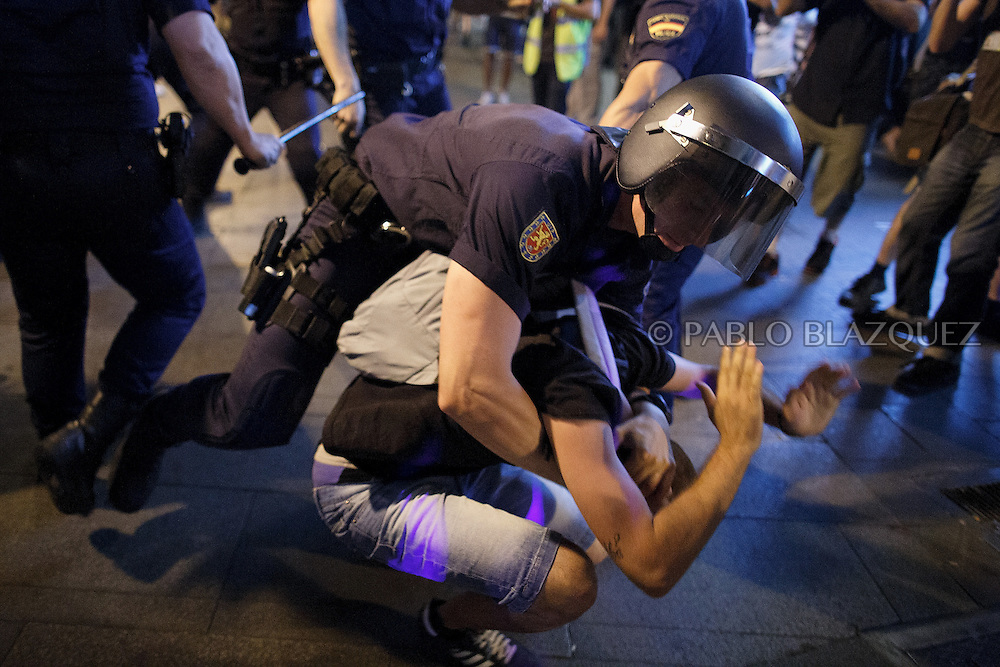 A riot policeman puts down a protestor at Gran Via during a demonstration against the Spanish government, on Thursday, July 18, 2013, in Madrid, Spain. Thousands demonstrators demanding the resignation of Prime Minister Mariano Rajoy and its party gathered in front of the People's Party headquarter. Rajoy rejected demands to resign after more alleged secret payments and test messages related to former political party treasurer Luis Barcenas under investigation appeared. The spectacle of alleged greed and corruption has enraged Spaniards hurting from austerity and sky high unemployment.