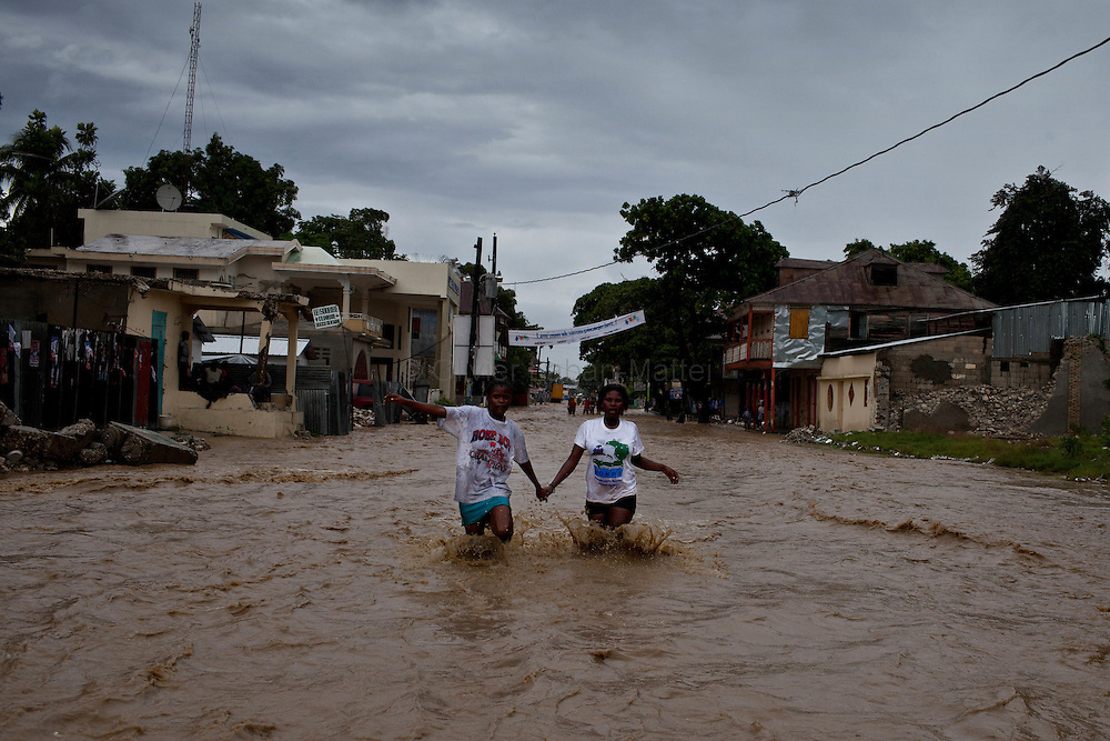 After hurricane Tomas went through Haiti, the city of Leogane has been totally flooded by the heavy rain and the overflow of the river Roullorne.///Two Haitian girls walk in the the muddy water, in a street of Leogane during hurricane Tomas.
