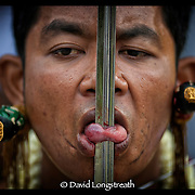 """In this """"Signature Series"""" image by David Longstreath, a devotee has his tounge pierced as part of the Phuket, Thailand, Vegetarian Festival.  he annual festival in Phuket is held on a annual basis and begins usually in late September of early October depending on the lunar cycle."""