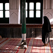 A woman in burkah prays behind a man at the Shah-i-hamadan shrine in Kashmir, India.