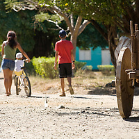 An ox cart rests by the side of the road as a family walks by in rural Guanacaste, Costa Rica. Ox carts have been used in Guanacaste for hundreds of years. Although few are still built, all are used on a daily basis.