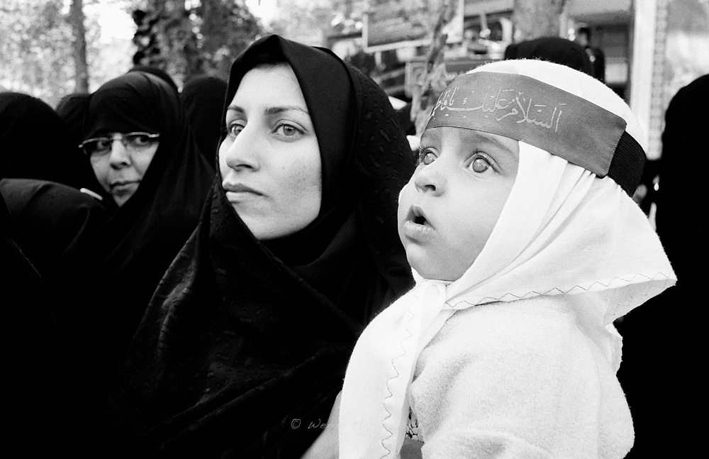 An Iranian mother in black chador with her baby on her arm during a ceremony for 65 martyr's from the Iran-Iraq war, whose bodies were recently discovered. Tehran, Iran, 2007