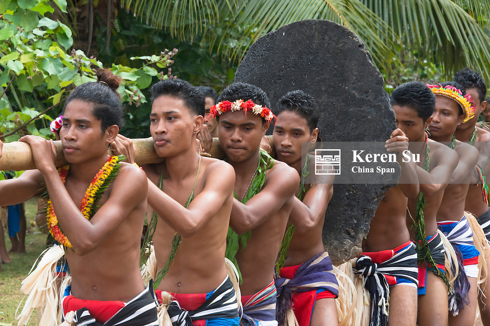 Yapese men in traditional clothing carrying stone money with log at Yap Day Festival, Yap Island, Federated States of Micronesia