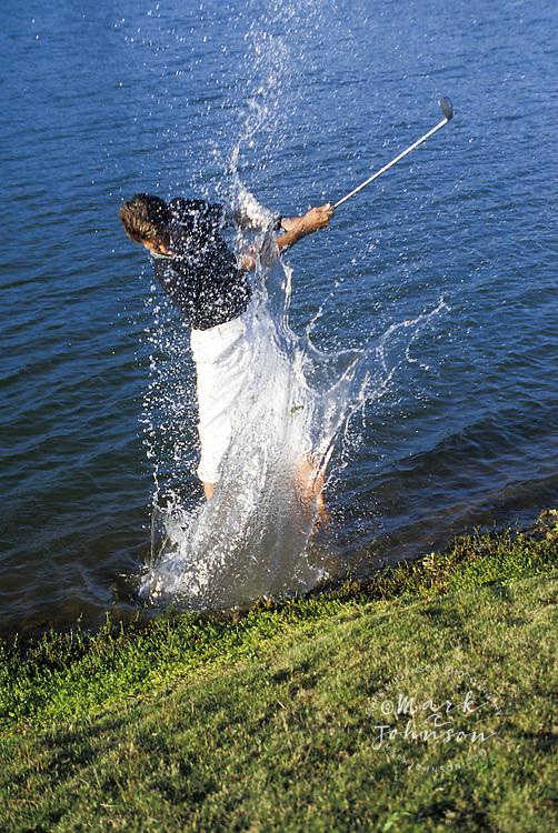 Golfer hitting ball out of water hazard, Kauai, Hawaii, USA,