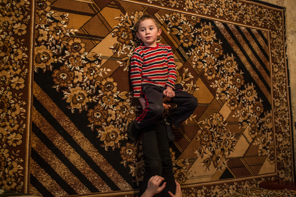 Nazar, 6, perches on the feet of his cousin Lyuda, 10, in the apartment where they live with their grandmother and two other cousins (not pictured) on Sunday, December 13, 2015 in Popasna, Ukraine. Nazar's mother was killed by shelling earlier in the year in Pervomaisk, a rebel-controlled city that saw very heavy fighting and where Nazar's father still lives.