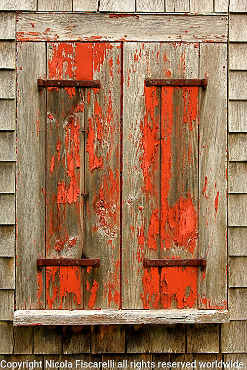 An old weathered painted window shutters on the abandoned  colonial house in Cape Cod Massachusetts.