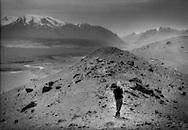 Man wearing traditional Kyrgyz hat walks above a wide glacial valley over 3,600m high in a Pamir Mountain Valley, Chinese Turkestan.  The glaciers of the Pamir, Kunlun and Tian Shan Mountains make it possible to live in the oases of the Taklamakan Desert.  The valley below, long ago, was filled with a glacier and as the present day glaciers recede due to global warming, there will continue to be less and less water for the Turkic peoples who live in the valleys and desert below to live.