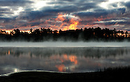 Fog beginning to rise off a lake in northern Wisconsin in the early dawn in October is lit by the rising sun briefly, making it to appear like fire over the still dark forest.