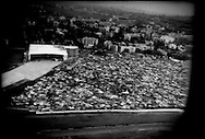 Massive shanty city, seen from airplane window during take off, pushes right up to runway of Chhatrapati Shivaji International Airport in Mumbai, India.  An estimated 50% of Mumbaikars live in slums.