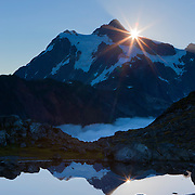 "The sun rises over Mount Shuksan, a 9,127-foot (2,782-meter) peak located in North Cascades National Park, Washington. Shuksan is derived from a Skagit Indian word meaning ""rocky and precipitous."" The mountain is reflected in a tarn near Artist Point."