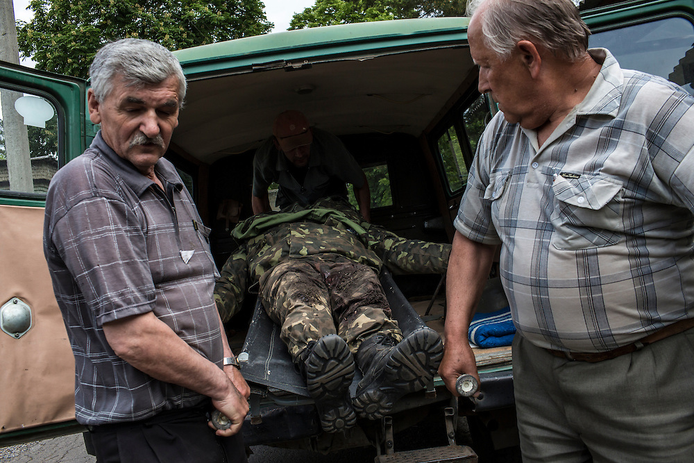 VOLNOVAKHA, UKRAINE - MAY 22:  The body of a Ukrainian soldier killed during an attack on a military checkpoint earlier in the day by unknown forces is carried into the morgue on May 22, 2014 in Volnovakha, Ukraine. Authorities reported fifteen soldiers were killed and 31 injured. (Photo by Brendan Hoffman/Getty Images) *** Local Caption ***
