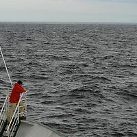 Cliffs and rocky shoreline along the southern part of Baffin Island, on the Hudson Strait. Meta Incognita Peninsula, Tourist enjoys an adventure cruise, Southern Baffin Island. Canadian Arctic. Arctic Ocean.