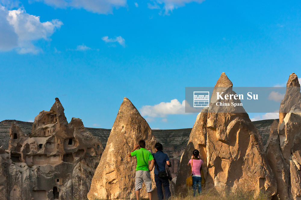 Tourists watching houses carved into the rock formations in the valley, Goreme National Park, Cappadocia, Turkey