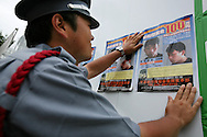 A security guard fixes to the wall of the British Embassy 'Wanted' posters, offering a 1 million Yen reward (approx 4,000 GBP) for information leading to the arrest of Tatsuya Ichihashi, suspected murderer of UK national Lindsay Hawker, Tokyo, Japan, on Friday 29th  June 2007.  LIndsay Hawker was murdered, and the suspect Tatsuya Ichihashi is still on the run, wanted by the police in connection with the murder.