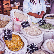 A farmers market at Chillan sells sacks of beans and corn in the Bio Bio Region, Chile, South America. A young Chilean girl takes sales orders.