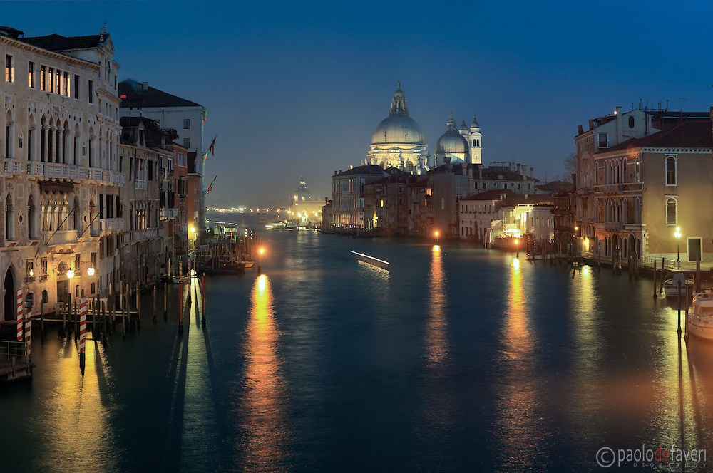 A view by night of the Grand Canal with the Church of the Salute and Punta della dogana in the background. Taken from the bridge of Accademia on an misty evening of mid January, this is stitched from nine vertical frames.