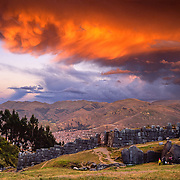 """The last orange light of sunset highlights turbulent clouds over the finely crafted Inca walls of Sacsayhuaman (Saqsaywaman), a """"Royal House of the Sun"""" built on a hill above Cuzco (Cusco or Qosqo), in Peru, South America. Cuzco was the site of the historic capital of the Inca Empire from the 1200s to 1532 and was honored on the World Heritage List in 1983 by UNESCO. Francisco Pizarro officially founded Spanish Cuzco in 1534. Cuzco is the longest continuously occupied city in the Americas and is built upon the foundations of the Incas (at 3400 meters or 11,200 feet elevation). The natural light sunset was captured on Fujichrome Velvia film. Licensed by National Geographic Maps in 2008 for a Geotourism Map of Peru's Sacred Valley."""