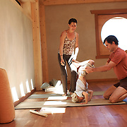 Tias and Surya Little and their son, Eno, play around in their yoga studio