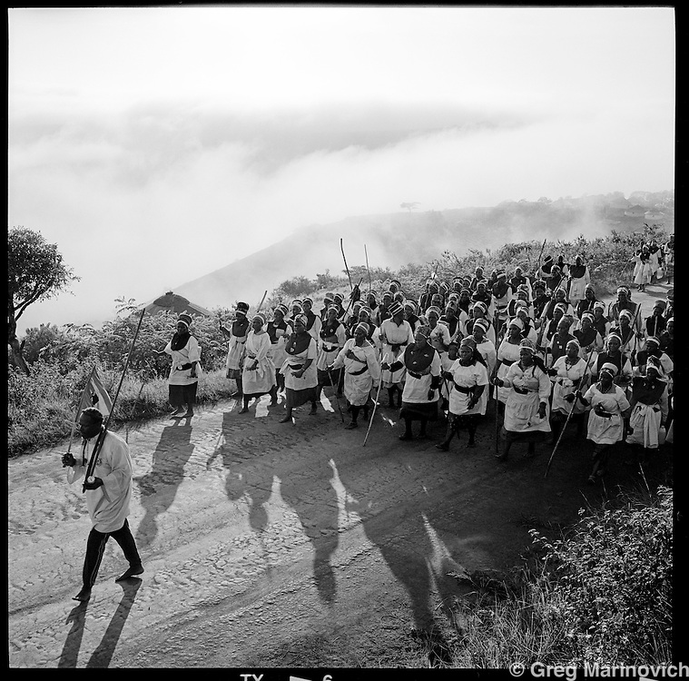 Members of the Nazaeth baptist Church rush along a sand road on the first day their annual three day bare-foot pilgrimage from the church headquarters near KwaMashu to the holy mountain of Nhlangakazi, KwaZulu natal, January 1998. The pigrimage traces th footsteps and pays homage at shrines of the founder Isaiah Shembe's 1913 journey of enlightenment. Photo Greg Marinovich