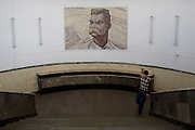 Man emerges from a subway station below mural of stalin, moscow 2007