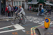 A cyclist wearing a stylish suit pedals over road junction construction markings in Soho, central London.