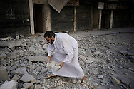 SYRIA, ALEPPO : A man helps to clean the road by rubble, after a jet fighter dropped a bomb on the building in front of the Dera al-Shifa hospital in the northern city of Aleppo, on September 23, 2012. ALESSIO ROMENZI