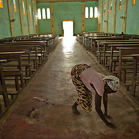Woman cleaning the All Saints Church in Rajef, Sudan. Built in 1919 by Italian priests, this is one of the older Catholic churches in Sudan.