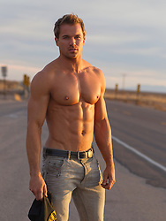shirtless man with a flawless body standing on a road wearing only jeans