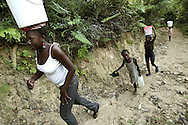 Youg girls walk up the mountainside with buckes of water they filled at the natural spring high on the mountain above Carrefour, Haiti.  The young girls of the family are usually asked to carry this laborious task, with walks often over 2 hours long each way from the spring.