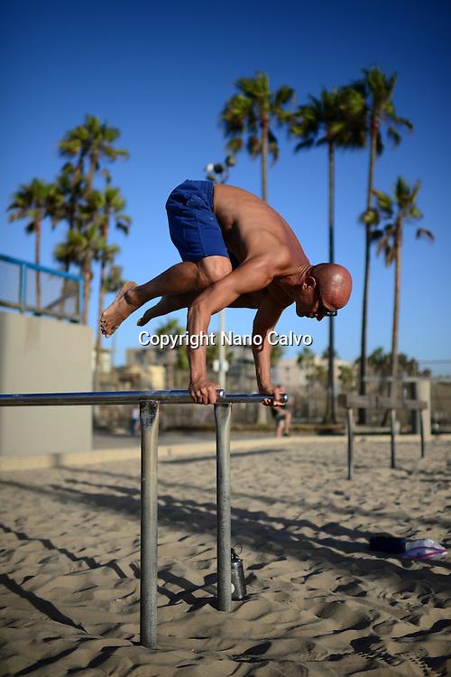 Young man training in Venice Beach Calisthenics park, California.