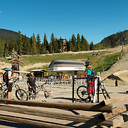 Downhill bike riders at the base of the Whistler Blackcomb Bike Park.  Whistler Village, Whistler BC, Canada.