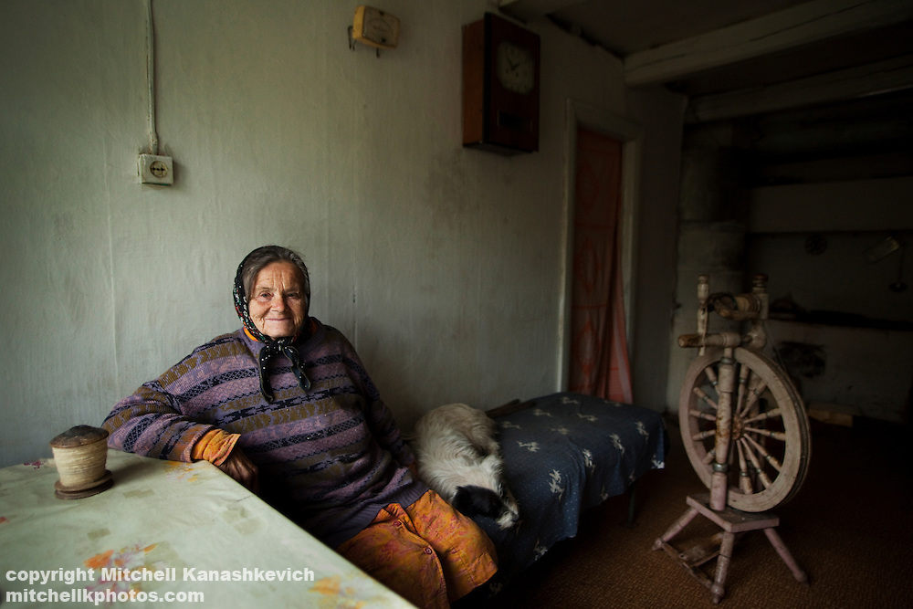 Elderly Belarusian woman with a pet dog and a traditional spinning wheel