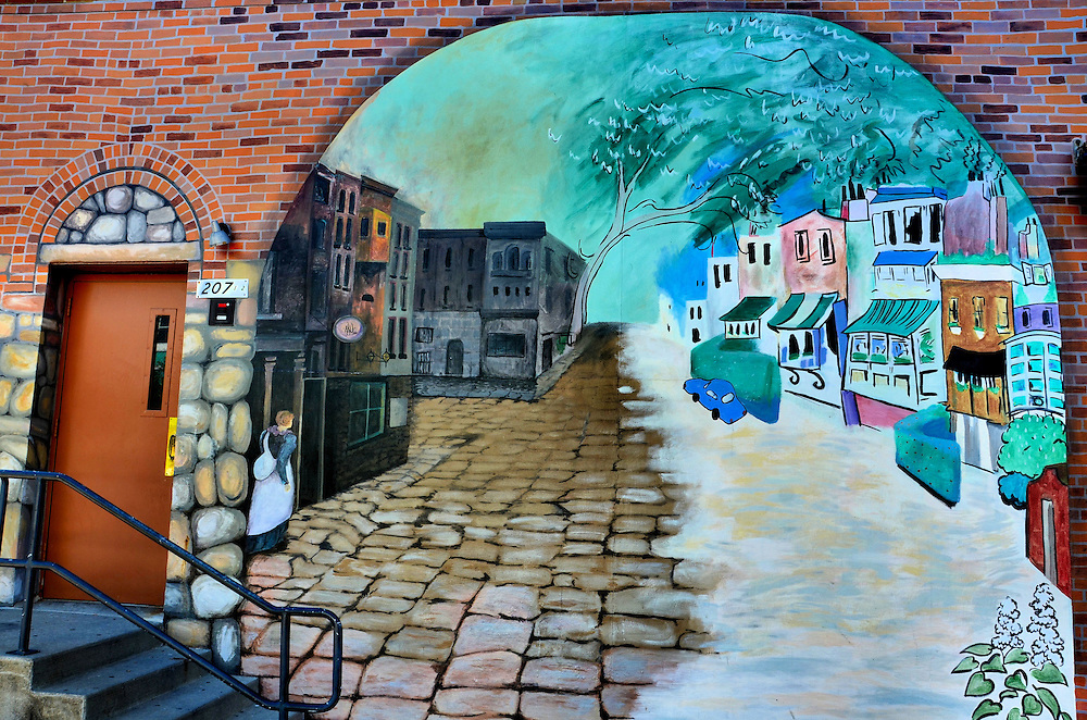 Medicine for the Soul Mural by Anna Sorey in Iowa City, Iowa<br /> This lovely mural in downtown Iowa City near the University of Iowa campus is called &ldquo;Medicine for the Soul.&rdquo; The painting by Anna Sorey shows a simple town scene during two seasons: winter and summer. The bricks and stones are part of the mural but the door and staircase are real. The artwork was commissioned by Sandra Navalesi.