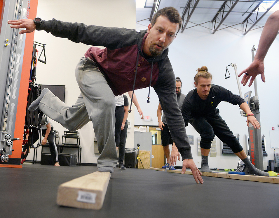 """gbs040217f/GO -- Jude Maulton of Albuquerque, left, and Trey Casaus of Albuquerque, right, work on 2x4 inch beams during a MoveNat workshop at Elevate where coaches learn how to incorporate this type of movement """"play"""" into strength and conditioning programs. MoveNat is a comprehensive, holistic and mindful approach to the full range of natural human movement abilities. (Greg Sorber/Albuquerque Journal)"""