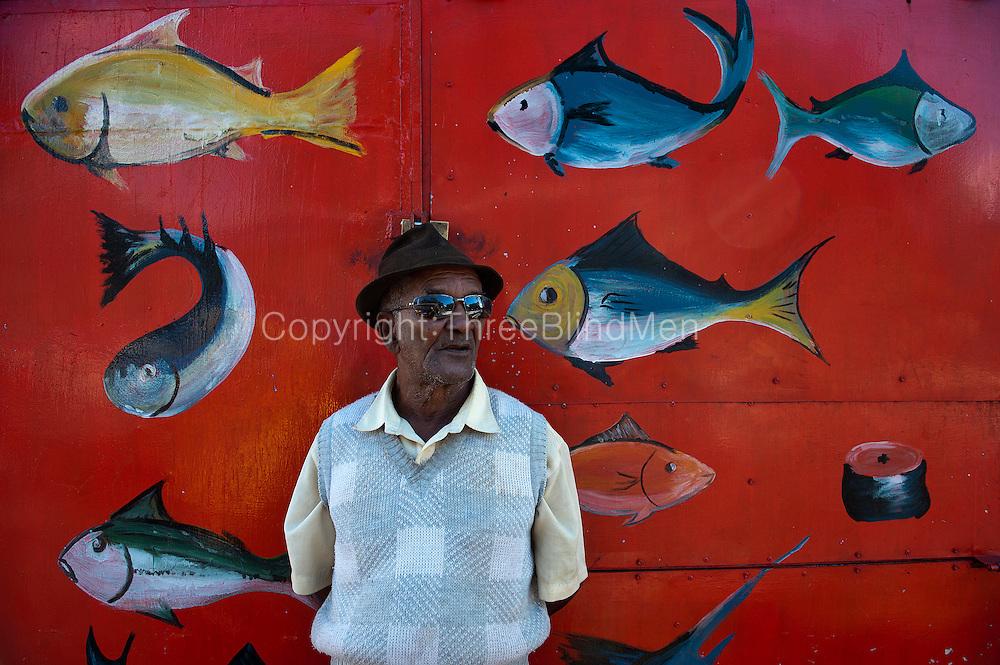 Mauritius. Man at fish stall in Abercrombie.