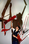 """November 18, 2002 - Artist Luca Buvoli hangs his sculpture """"Vector 2"""" made of resin and dye in the gallery at PICA. The concept of the show is a supposition that human flight is possible and described through diagrams, installations and a movie."""