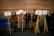 People hold signs outside the Spin Room following a debate in Manchester, N.H., on Saturday, Jan. 5, 2008.
