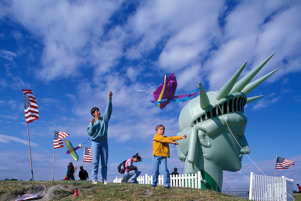 USA, Washington, Seattle, Family flies kite by inflated Statue of Liberty on hilltop in Gasworks Park on July 4th weekend