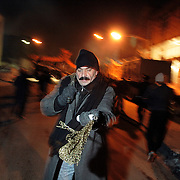 Night celebrations in the street.A man hits himself whit the chains in sign of mourning....